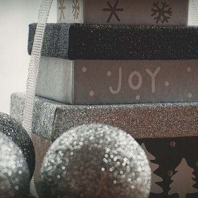 Stack of silver presents with the words Joy